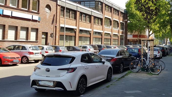 Foto einer Straße mit vielen parkenden Autos
